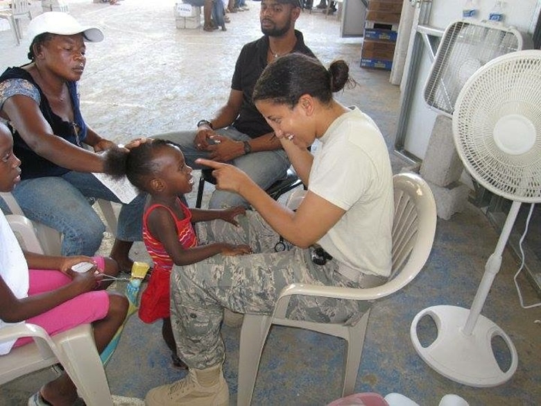 Maj. Khadidja Harrell, Chief Global Health Engagement at U.S. Pacific Command, checks up on a young patient in Haiti, May 2010. Harrell, who is a pediatrician by trade, visited with many patients as part of a medical readiness training exercise after the 2010 Haiti earthquake. (Courtesy photo)