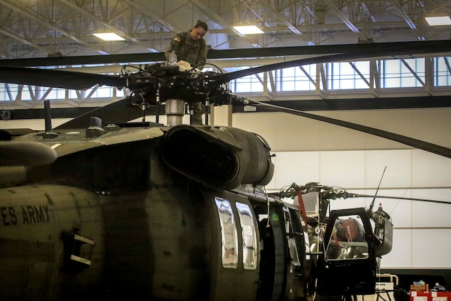 A soldier performs maintenance on the main rotor blades of a helicopter.