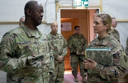Brig. Gen. Sylvester Cannon, commanding general of the 135th Sustainment Command, and deputy commanding general of the 1st Theater Sustainment Command-OCP, left, is briefed by 1st Lt. Keerstin Beitter, deputy chief of the 49th Theater Gateway and officer-in-charge of the Camp Buehring gateway.