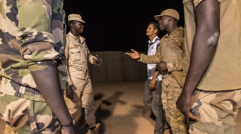 U.S. Air Force Staff Sgt. Mackenzie Isidor, 822nd Expeditionary Base Defense Squadron fire team leader, communicates with members of the Forces Armées Nigeriennes, during a night shift at Nigerien Air Base 201, in Agadez, Niger, Feb. 26, 2018. The U.S. military is in Agadez at the request of the Government of Niger, and the U.S. remain committed to helping our African partners protect their borders with matters of national security, and with other efforts important to the citizens of Niger. (U.S. Air Force photo by Tech. Sgt. Nick Wilson)