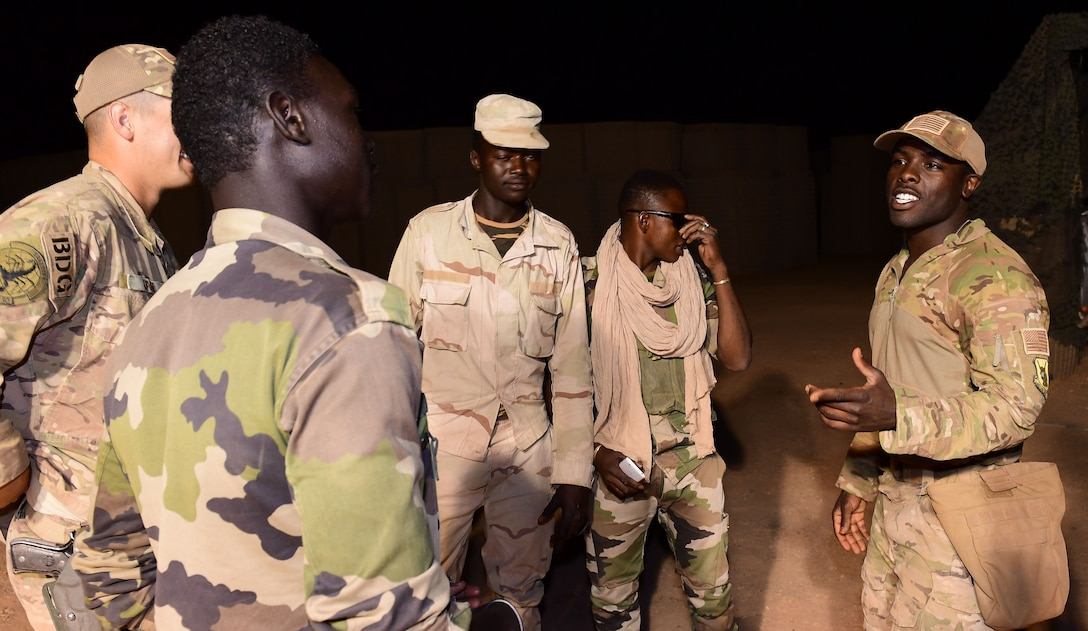 U.S. Air Force Staff Sgt. Mackenzie Isidor, 822nd Expeditionary Base Defense Squadron fire team leader, briefs Airmen and members of the Forces Armées Nigeriennes, during a night shift at Nigerien Air Base 201, in Agadez, Niger, Feb. 26, 2018. Airmen and their host nation partners in Africa work closely in an effort to support mutual security goals and objectives in Africa. (U.S. Air Force photo by Tech. Sgt. Nick Wilson)