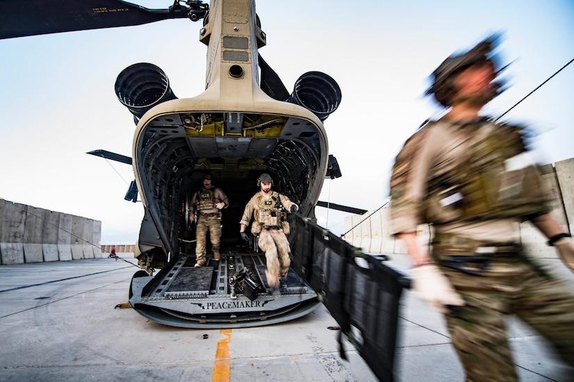 Airmen leave the back on an aircraft.