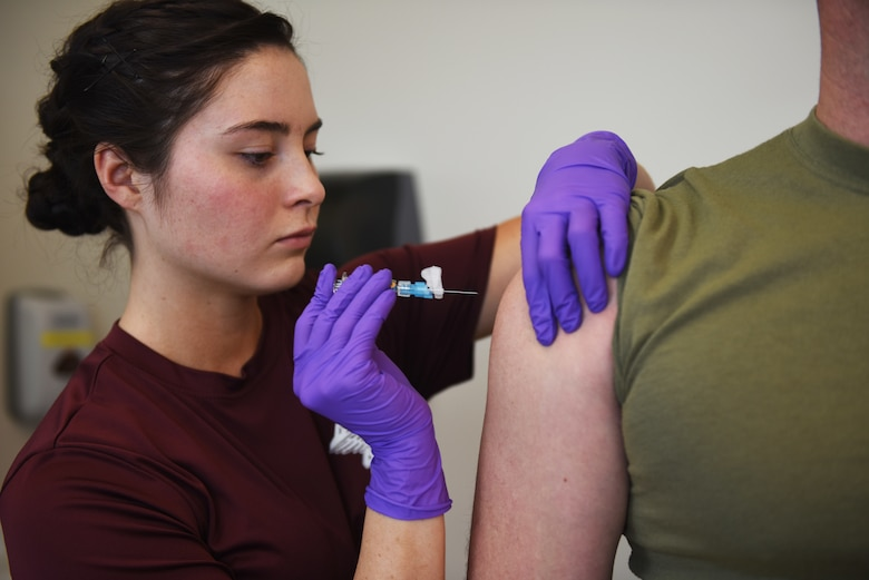 """Airman 1st Class Kayla Jaramillo, an aerospace medical technician at the Buckley Air Force Base Colfax Clinic, in Aurora, Colorado administers a vaccine to a patient Feb 9, 2018. Out of hundreds of paintings submitted for the 2017 Air Force Art Contest, Jaramillo placed first in the Adult Novice Category with a painting she titled """"Swallow your Pride, Life isn't Fair"""". (U.S. Air Force photo by Senior Airman Jessica B. Kind)"""