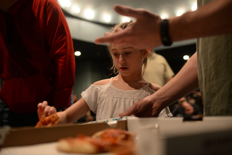 A child picks a slice of pizza before watching a movie during a Hearts Apart event at the Elks Theater in Rapid City, S.D., March 3, 2018. Each quarter, the Airman and Family Readiness Center at Ellsworth Air Force Base, S.D., hosts an event like this, but the location and activity will vary. (U.S. Air Force photo by Airman 1st Class Nicolas Z. Erwin)