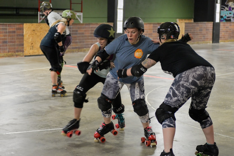 Tech Sgt. Stephanie Hawthorne, 16th Weather Squadron NCO in charge of the Model Operations Flight and team member of the Omaha Rollergirls, blocks another skater with her teammate during practice March 7, 2018, Omaha, Nebraska. Outside of the track, the Rollergirls volunteer their time to benefit charities such as the American Cancer Society, Youth Emergency Services and the Special Olympics. (U.S. Air Force photo by Paul Shirk)