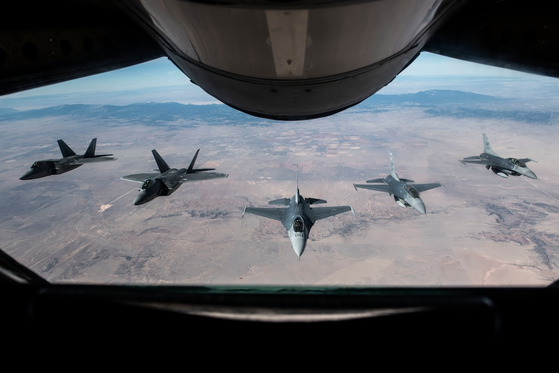 Two F-22 Raptors and three F-16 Fighting Falcons fly in formation behind a KC-135 Stratotanker while returning home from the Heritage Flight Training Course at Davis-Monthan Air Force Base, Ariz., March 5, 2018. The course brings pilots, maintainers and aircraft from various generations together to train for dissimilar formation flights to demonstrate the Air Force's history of airpower. (U.S. Air Force photo by Senior Airman Destinee Sweeney)