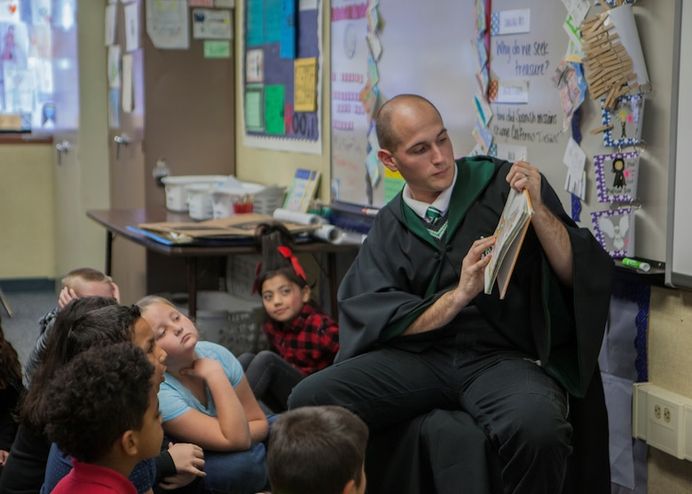 Cpl. Ryan Britton, Radio Technician with Headquarters and Service Battalion, 1st Tank Battalion, reads a book to students in support of Read Across America at Friendly Hills Elementary School in Joshua Tree, Calif., on March 2, 2018.  Read Across America is an annual reading motivation and awareness program that calls for every child in every community to celebrate reading. (U.S. Marine Corps Photo by Cpl. Francisco J. Britoramirez)