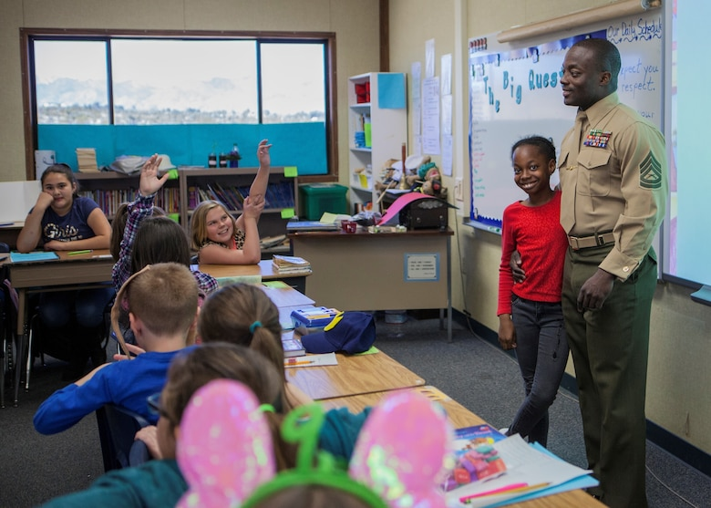 GySgt. Jared R Wright, Marine Training Unit Staff Non Commissioned Officer in Charge, Marine Training Unit, and daughter, Su'Myah K. Wright answer questions of students in support of Read Across America at Friendly Hills Elementary School in Joshua Tree, Calif., on March 2, 2018.  Read Across America is an annual reading motivation and awareness program that calls for every child in every community to celebrate reading. (U.S. Marine Corps Photo by Cpl. Francisco J. Britoramirez)