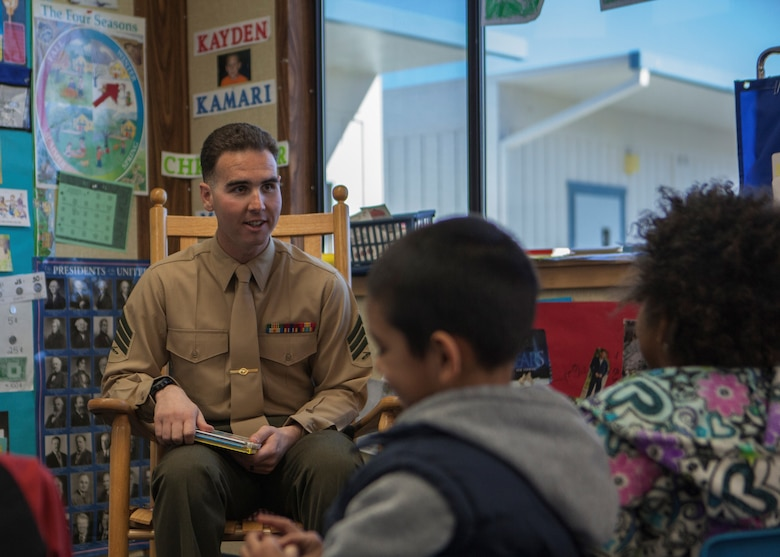 Sgt. Seth Laird, Range Safety Officer, with Marine Training Unit, converses with students in support of Read Across America at Friendly Hills Elementary School in Joshua Tree, Calif., on March 2, 2018.  Read Across America is an annual reading motivation and awareness program that calls for every child in every community to celebrate reading. (U.S. Marine Corps Photo by Cpl. Francisco J. Britoramirez)