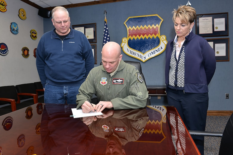 Timothy Slobodnik (L), 55th Civil Engineer Squadron and AFGE Local Chapter 1486 president and Shay Caris (R), 55th FSS Civilian Personnel Flight Labor Relations officer watch Col. Michael Manion, 55th Wing commander, sign a new collective bargaining agreement on March 7 at 55th Wing headquarters on Offutt Air Force Base, Nebraska.