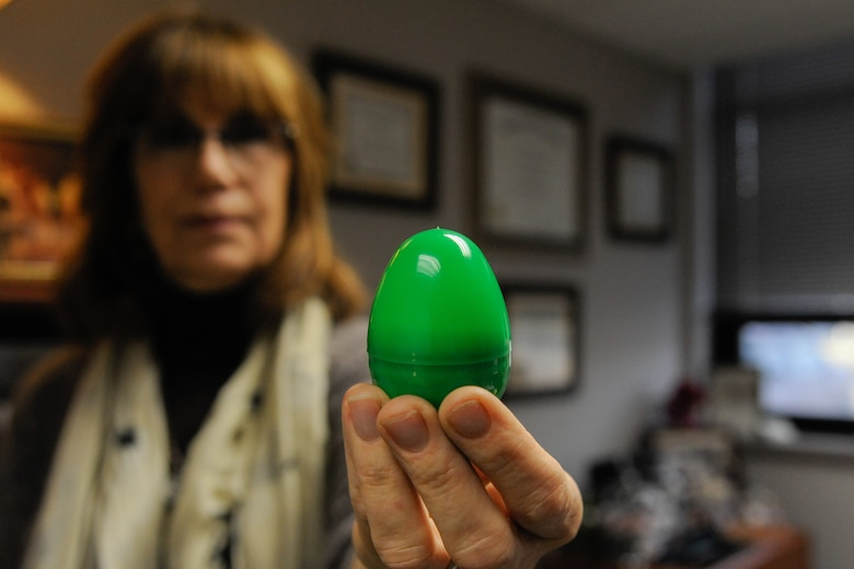 Vera Bowie, Violence Prevention Integrator, holds up one of the green eggs that will be hidden all over Wright-Patterson for this year's Spring Fling egg hunt. The hunt will be held from March 12-23 all over Area A and Area B. (U.S. Air Force Photo/Staff Sgt. Ashley Clingerman)