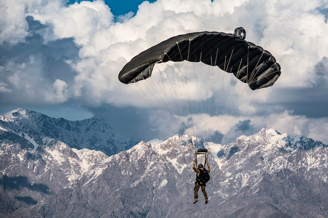 An airman parachutes against a backdrop of snow-capped mountain peaks and cloud-filled blue sky.