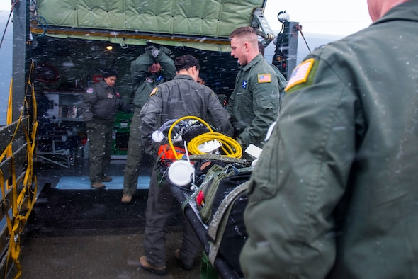 Airmen from the 375th Aeromedical Evacuation Squadron transport a patient litter onto a KC-135 Stratotanker during an aeromedical evacuation training at Fairchild Air Force Base, Washington, March 1, 2018. Practicing when to lift, move, stop and place equipment allows AE teams to maneuver patients with safety and efficiency. (U.S. Air Force photo/Airman 1st Class Whitney Laine)