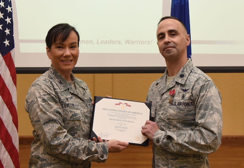 Col. Debra Lovette, 81st Training Wing commander, presents Maj. Jack Vilardi, 81st Medical Support Squadron TRICARE Operations and Patient Administration flight commander, with a certificate of recognition during a commander's all-call at the Bay Breeze Event Center March 5, 2018, on Keesler Air Force Base, Mississippi. Vilardi was presented with a Bronze Star for meritorious achievement while assigned to a surgical team deployed to Iraq, April 2017, through Oct. 2017. (U.S. Air Force photo by Kemberly Groue)