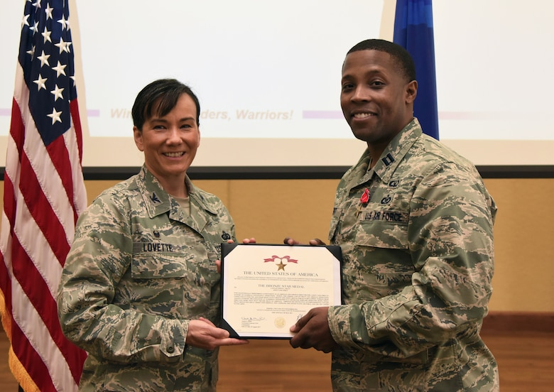 Col. Debra Lovette, 81st Training Wing commander, presents Capt. Edwin Pratt, 81st TRW executive officer, with a certificate of recognition during a commander's all-call at the Bay Breeze Event Center March 5, 2018, on Keesler Air Force Base, Mississippi. Pratt was presented with a Bronze Star for meritorious achievement May 2016, through Nov. 2016. (U.S. Air Force photo by Kemberly Groue)