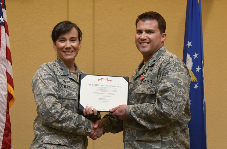 Col. Debra Lovette, 81st Training Wing commander, presents Lt. Col. Scott Eisenhuth, 81st Surgical Operations Squadron orthopedic surgeon, with a certificate of recognition during a commander's all-call at the Bay Breeze Event Center March 5, 2018, on Keesler Air Force Base, Mississippi. Eisenhuth was presented with a Bronze Star for meritorious achievement while assigned to a surgical team deployed to Iraq, April 2017, through Oct. 2017. (U.S. Air Force photo by Kemberly Groue)