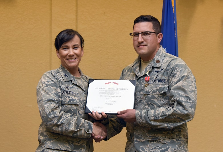 Col. Debra Lovette, 81st Training Wing commander, presents Maj. Ramon Riojas, 81st Surgical Operations Squadron general surgeon, with a certificate of recognition during a commander's all-call at the Bay Breeze Event Center March 5, 2018, on Keesler Air Force Base, Mississippi. Riojas was presented with a Bronze Star for meritorious achievement while assigned to a surgical team deployed to Iraq, April 2017, through Oct. 2017. (U.S. Air Force photo by Kemberly Groue)