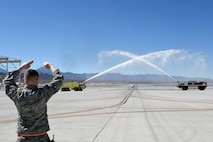 An MQ-1 Predator receives a water salute to commemorate its time in service and capabilities provided to combatant commanders and troops on the ground March 9, 2018, at Creech Air Force Base, Nev. Airmen have operated the MQ-1 for more than 20 years and provided intelligence, surveillance, reconnaissance and strike capabilities to the fight 24/7/365 across multiple areas of responsibilities. (U.S. Air Force photo by Senior Airman James Thompson)