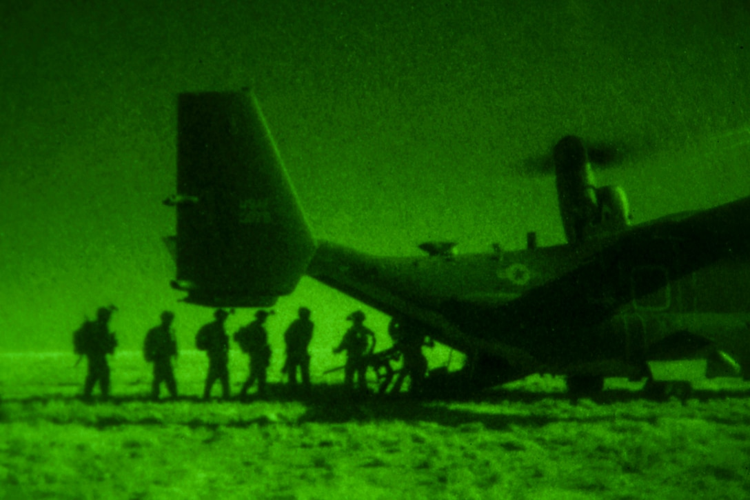 Soldiers, seen in silhouette in green light from a night vision device, board the back of an aircraft parked on flat terrain.