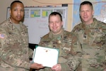 Army Capt. Jason M. Spalding, center, 21st Theater Sustainment Command liaison officer Mission Command Element receives an Army Commendation Medal from Army Brig. Gen. William L. Thigpen, left, the 4th Infantry Division's deputy commanding general, and Army Command Sgt. Maj. Eric B. Olsen, the division/MCE sergeant major, at the MCE's headquarters in Poznan, Poland, Feb. 19, 2018. Spalding has worked during his tour to improve living and working conditions for soldiers in support of the Atlantic Resolve mission. Army photo by Staff Sgt. Scott J. Evans