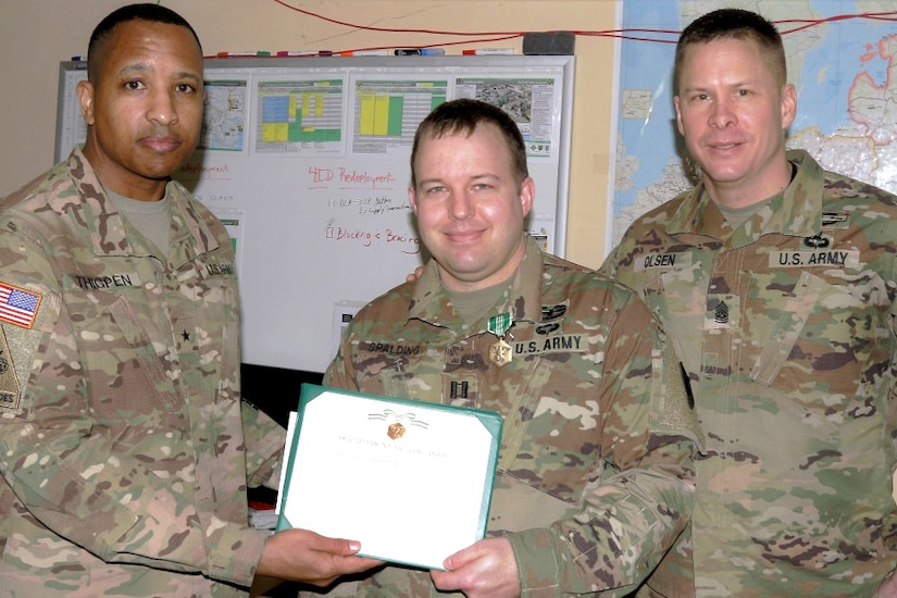 Three service members pose for a photograph with two holding a certificate.