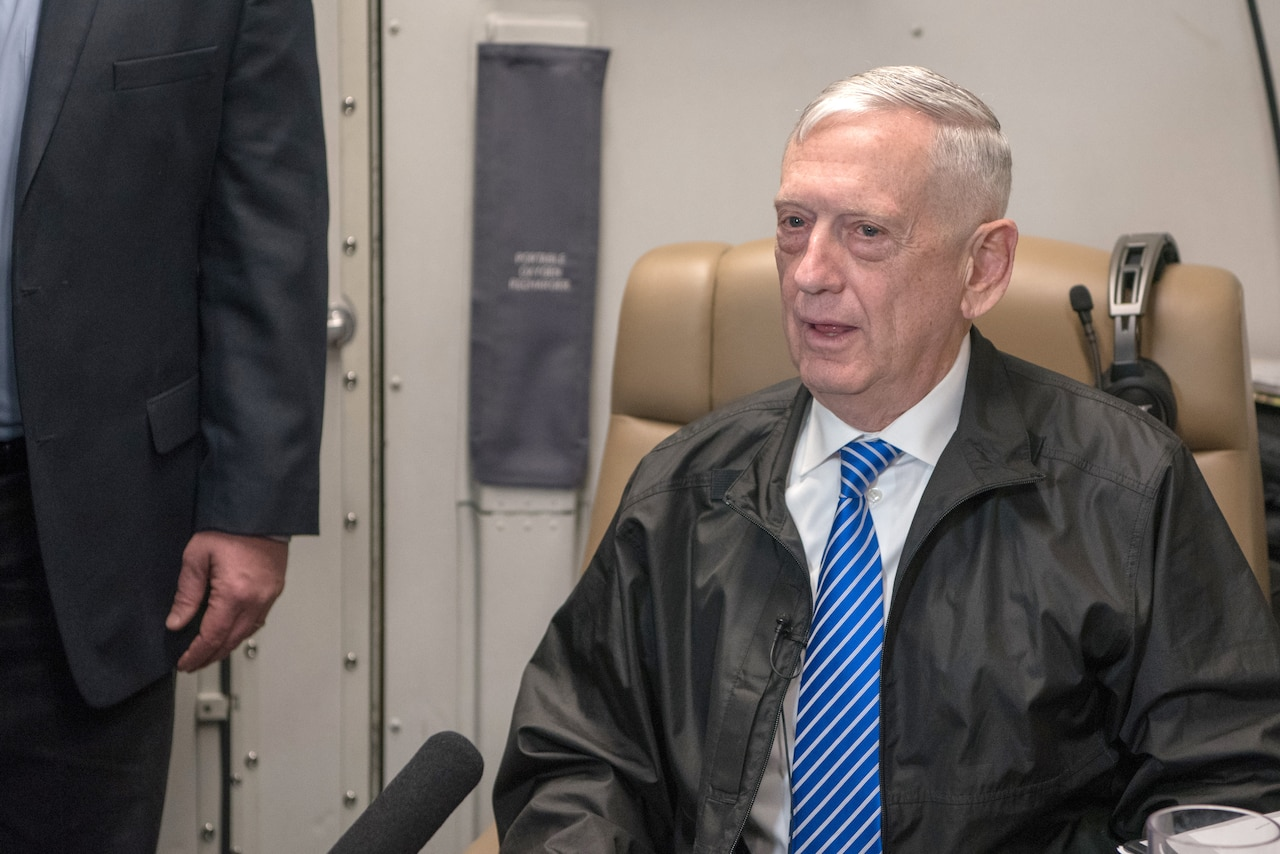 Defense Secretary James N. Mattis sits in an aircraft seat and talks.