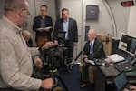 Defense secretary speaks with reporters in aircraft cabin.