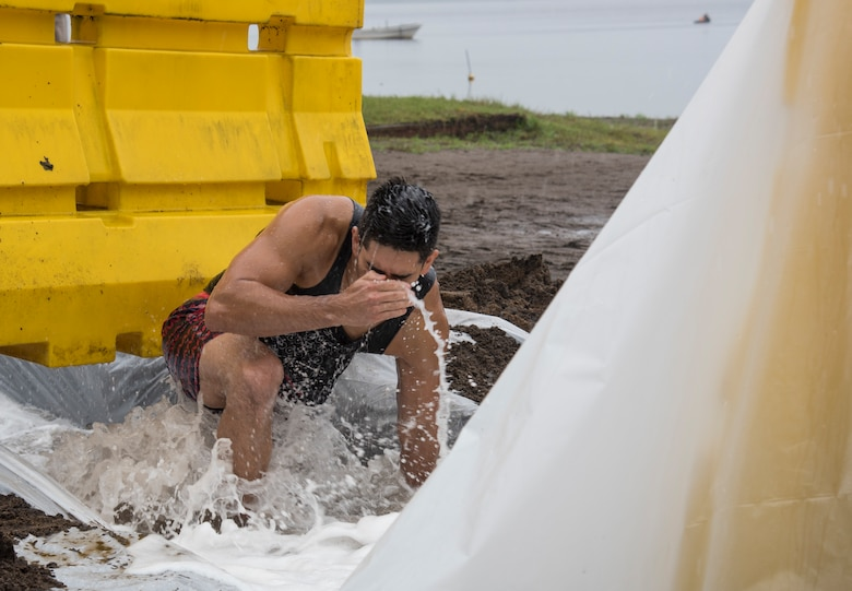 U.S. Navy Petty Officer 1st Class Andrew Morales, a Commander Task Force 72 information systems technician, slides through an obstacle as part of a regatta competition during the first Team Misawa Resilient Relationships and Appreciation Day, at Misawa Air Base, Japan, Aug. 18, 2017. The regatta, which is a boat racing competition, challenged personnel with working together to build their own boats, test its floatation and race in Lake Ogawara. The 35th Fighter Wing Chapel coordinated the event and tested teams' capabilities to think critically and work together, exercising their physical and mental pillars of resiliency, which service members incorporate in their daily career tasks. (U.S. Air Force photo by Senior Airman Sadie Colbert)