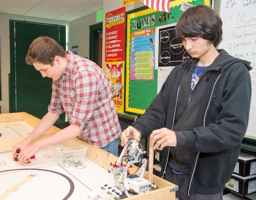 Cole High School students Mitchell Hafer (left) and Henry Yowell (right) set up a robotics competition board and robot in a classroom. Both students, members of the Cole robotics team, will be competing in the Texas Computer Educators Association State Robotics Challenge Contest April 7 at Hutto High School, near Austin.