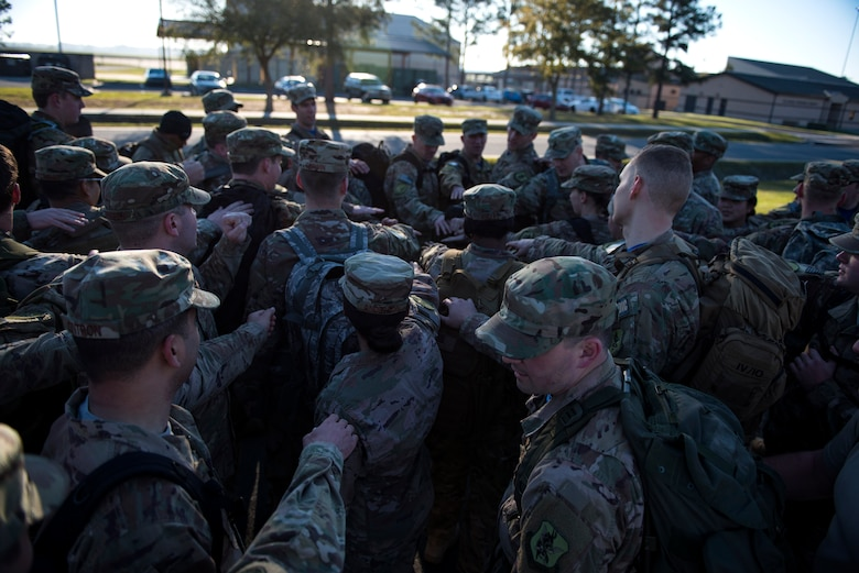 Airmen from the 347th Operations Support Squadron (OSS) rally together after a ruck march during a Comprehensive Airman Fitness (CAF) Day, March 9, 2018, at Moody Air Force Base, Ga. During CAF Day, the 347th OSS focused on the physical domain, bolstering resiliency through team building activities. (U.S. Air Force photo by Airman 1st Class Erick Requadt)