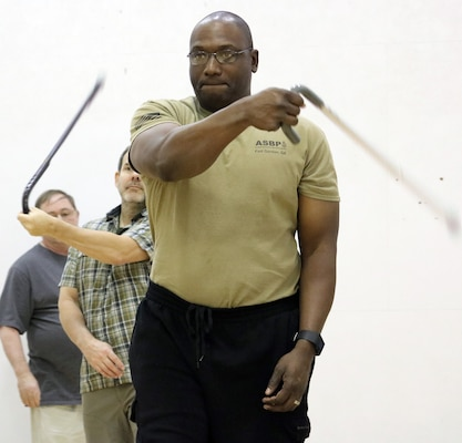 Chief Warrant Officer 3 Robert Hunter, Brooke Army Medical Center Warrior Transition Battalion, puts his cane self-defense tactics to use during a training session Feb. 3, in the Jimmy Brought Fitness Center, Joint Base San Antonio-Fort Sam Houston. Hunter was one of 40 active duty service members, wounded warriors, veterans and family members who attended the three-hour session to learn the intricacies of cane self-defense.
