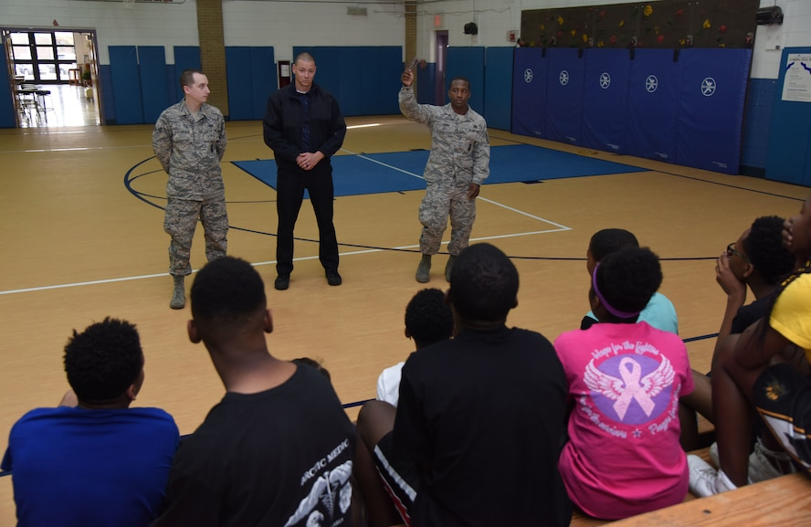 Senior Airman James Vaughn, 81st Security Forces Squadron training instructor, Justin Depew, 81st SFS patrolman, and Master Sgt. Cordarius Lewis, 81st SFS operations NCO in charge, discuss safety procedures during lockdown training at the Keesler Youth Center March 8, 2018, on Keesler Air Force Base, Mississippi. In lieu of recent active shooter incidents in schools, defenders conducted the training to discuss school safety during a potential active shooter situation. (U.S. Air Force photo by Kemberly Groue)