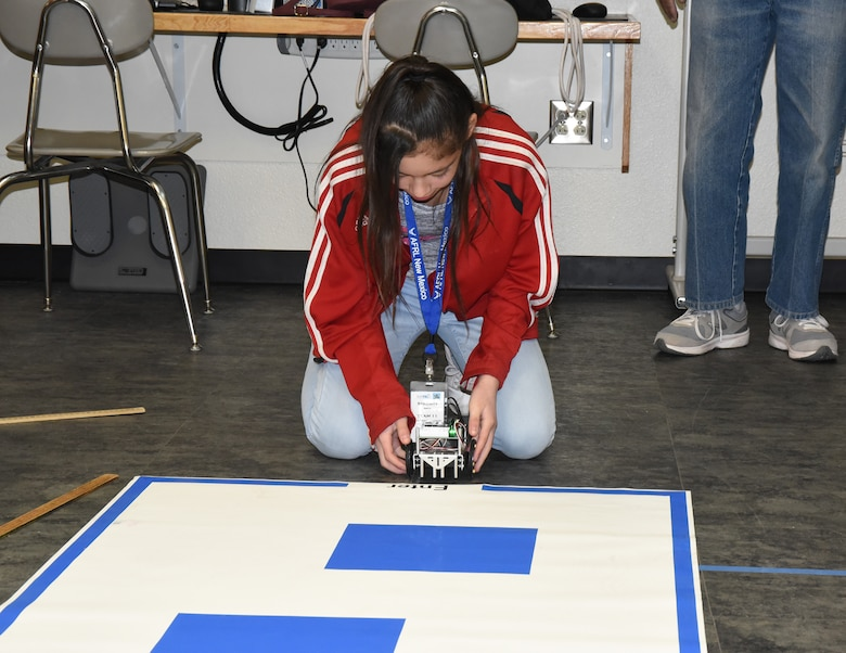 After programming her robot, Serenity Smith, a sixth grader from Mesa View Elementary School, tests it on a simple maze at the Air Force Research Laboratory's La Luz Academy Robotic Challenge Expo March 9 at Kirtland. Smith was one of more than 100 students from around the state that competed at the event.