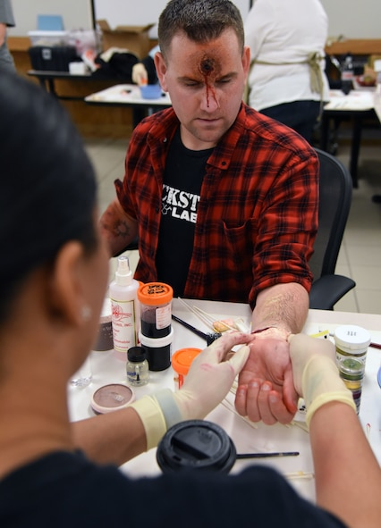 """Staff Sgt. Dominque Mason, 81st Medical Operations Squadron neurodiagnostic technologist, applies moulage to Staff Sgt. Matthew Clinesmight, 81st Security Forces Squadron evaluator, during a training session at Allee Hall March 8, 2018, on Keesler Air Force Base, Mississippi. The session was held to teach volunteers how to apply moulage on exercise """"casualties"""" to provide emergency responders with a more realistic training experience. (U.S. Air Force photo by Kemberly Groue)"""