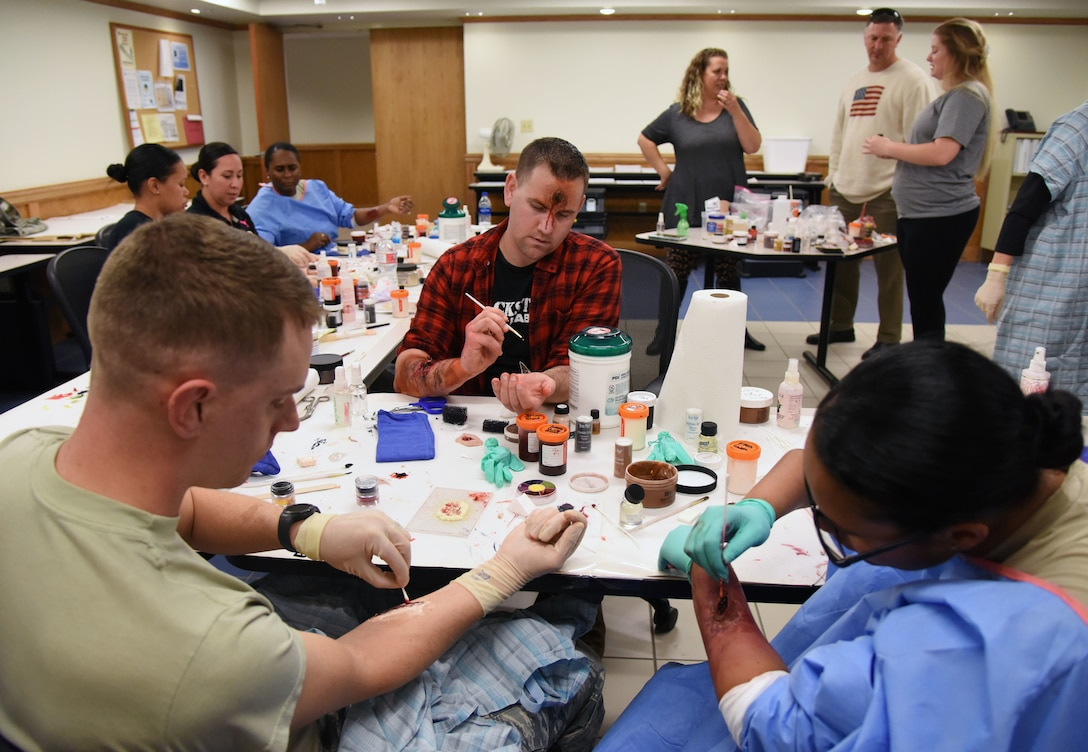 """Volunteers learn how to apply moulage during a training session at Allee Hall March 8, 2018, on Keesler Air Force Base, Mississippi. The session was held to teach volunteers how to apply moulage on exercise """"casualties"""" to provide emergency responders with a more realistic training experience. (U.S. Air Force photo by Kemberly Groue)"""