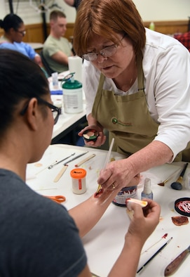 "Regina Parker, 81st Medical Operations Squadron mental health secretary and moulage co-team lead, applies moulage to Mayra Guerra, 81st Training Wing wing inspection team manager, during a training session at Allee Hall March 8, 2018, on Keesler Air Force Base, Mississippi. The session was held to teach volunteers how to apply moulage on exercise ""casualties"" to provide emergency responders with a more realistic training experience. (U.S. Air Force photo by Kemberly Groue)"