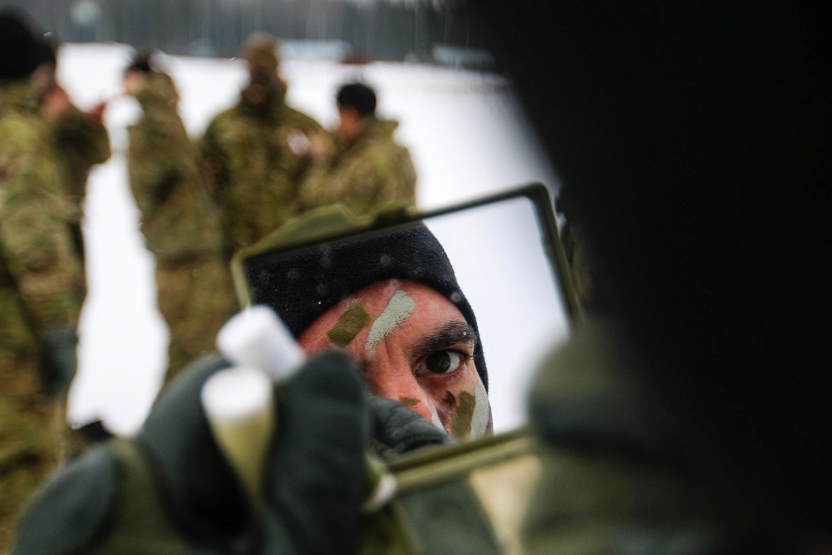 A soldier, whose face is visible in a hand-held mirror, applies camouflage paint in a snowy field with soldiers gathered nearby.