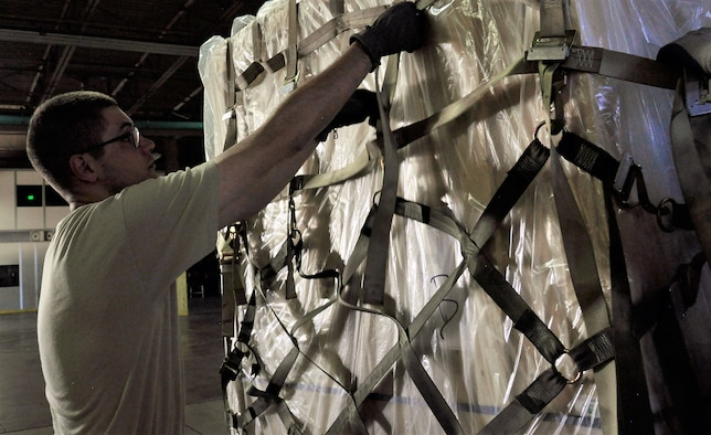 A 39th Aerial Port Squadron reservist secures netting around a cargo shipment during annual tour training at Travis Air Force Base, California, July 2017. The 39th APS was recently awarded the Air Reserve Component Air Transportation Activity of the Year in 2017 for outstanding contributions to the success of the Air Force and Department of Defense missions. (U.S. Air Force photo by Staff Sgt. Frank Casciotta)