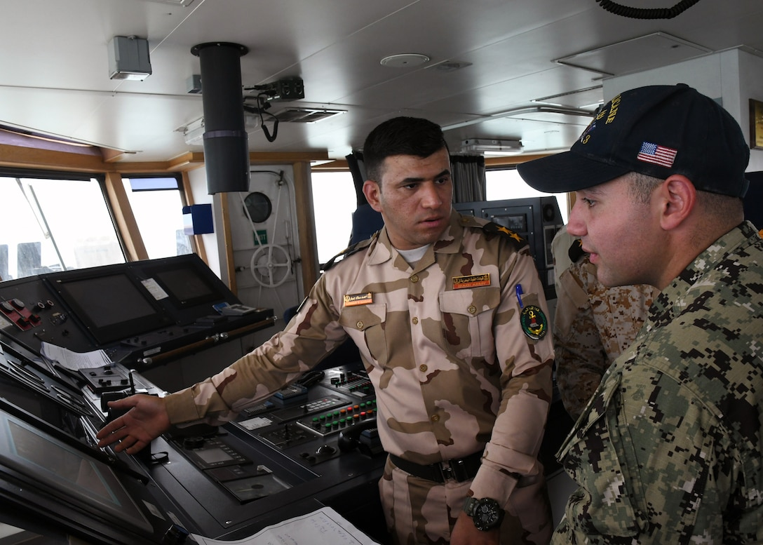 (Feb. 21, 2018) Iraqi navy 1st Lt. Ahmad Gabar (left), second mate of Iraqi offshore support vessel Al Basra (401), explains Al Basra's bridge watch stations to Gunner's Mate Seaman Steven Saikaly, a Sailor assigned to coastal patrol ship USS Hurricane (PC 3), during a trilateral exercise with Iraq and Kuwait. The exercise is a surface engagement between the U.S. Navy, Iraqi navy, Kuwaiti navy and coast guard focused on improving proficiency in maritime security tactics to help ensure the freedom of navigation throughout the U.S. 5th Fleet area of operations. (U.S. Navy photo by Mass Communication Specialist 1st Class Bryan Neal Blair/Released)