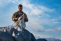 A U.S. Air Force combat rescue officer, assigned to the 83rd Expeditionary Rescue Squadron, Bagram Airfield, Afghanistan, field packs his parachute at the drop zone after a high altitude, high opening military free fall jump working with a C-130J Super Hercules flown by the 774th Expeditionary Airlift Squadron, Bagram Airfield, Afghanistan, March 4, 2018. Guardian Angel Team members conduct training on all aspects of combat, medical procedures and search and rescue tactics to hone their skills, providing the highest level of tactical capabilities to combatant commanders. (U.S. Air Force Courtesy Photo Edited by Tech. Sgt. Gregory Brook)