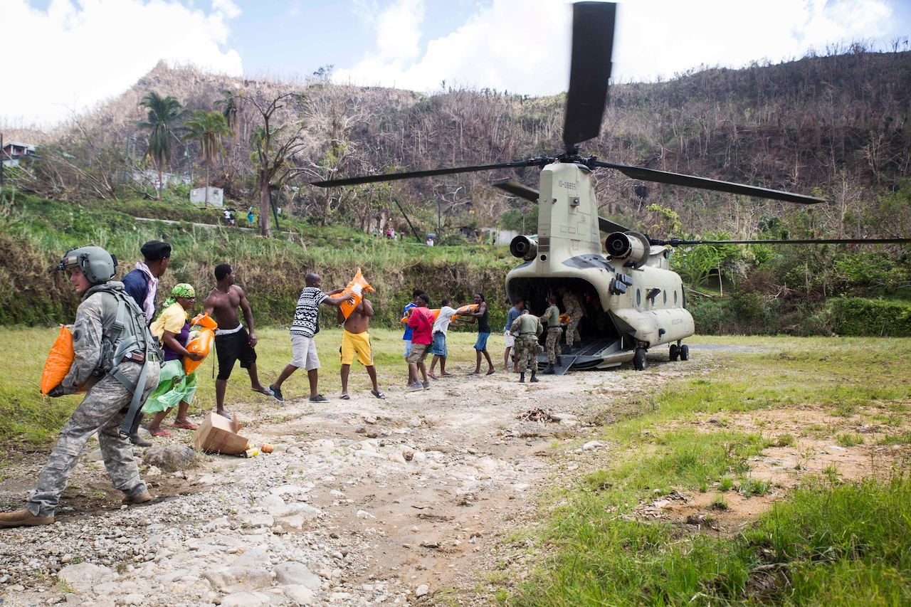 Army Sgt. Delton Reynolds, left, a flight engineer with Joint Task Force Leeward Islands, joins a chain with local residents and members of the Jamaican defense force to unload relief supplies from a CH-47 Chinook helicopter at Wotten Waven, Dominica.