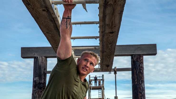 A sailor hangs from one arm on a bar obstacle.