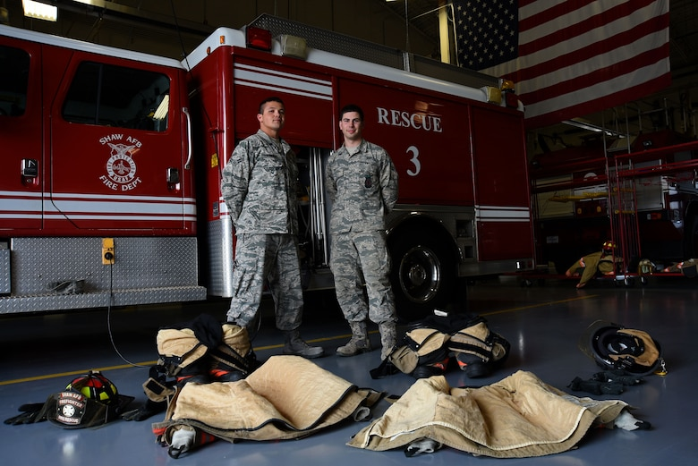 U.S. Air Force Airmen 1st Class Nicholas Denning, left, and Trevor Britt, 20th Civil Engineer Squadron firefighters, stand behind their gear at Shaw Air Force Base, S.C., March 8, 2018.