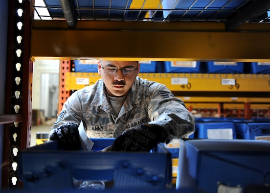 A male leans on blue containers with parts in a warehouse.