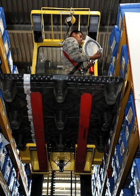 A male stands on a yellow forklift in a warehouse high in the air.