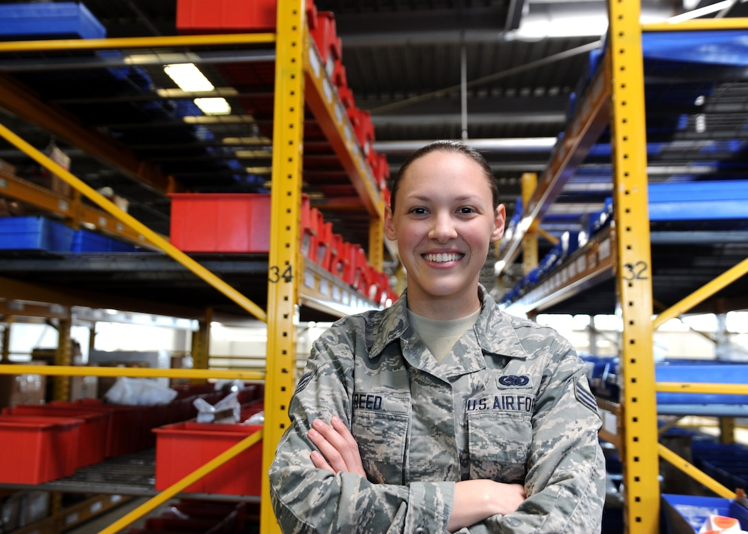 A smiling female stands in front of yellow shelves housing aircraft parts in a large warehouse.