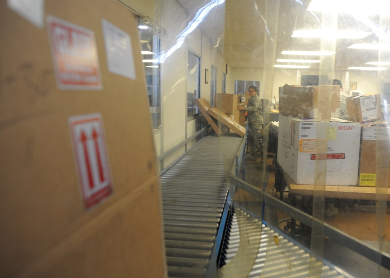 A cardboard box sits on a conveyor belt in a warehouse.