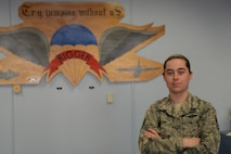 Woman in the Airman Battle Uniform stands with her arms folded in front of a parachute sign.