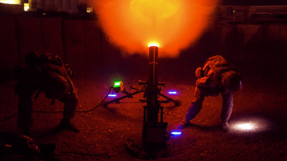Orange flames burst from a howitzer, illuminating a night sky, as Marines crouch on either side of the weapon.