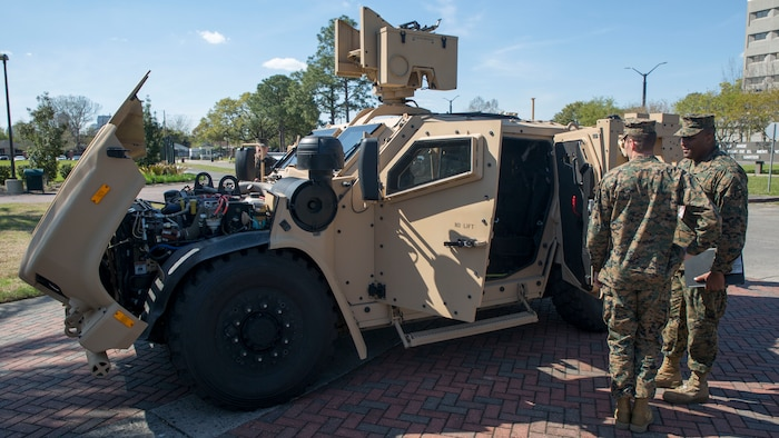 Marines at Marine Forces Reserve examine the inner workings of the Joint Light Tactical Vehicle after attending the JLTV roadshow executive brief at Marine Forces Reserve, New Orleans, La., March 9, 2018. The JLTV is the next evolution in tactical vehicles for the Marine Corps and will be introduced into circulation as early as the beginning of 2019 for the active component and will be fielded to the Reserve component in 2021. (U.S. Marine Corps photo by Sgt. Adwin Esters)